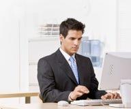 Hombre de negocios que pulsa en el ordenador Fotografía de archivo libre de regalías