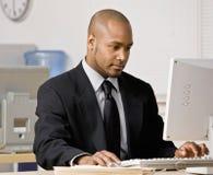Hombre de negocios que pulsa en el ordenador en el escritorio imagen de archivo