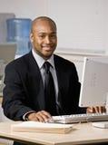 Hombre de negocios que pulsa en el ordenador en el escritorio imágenes de archivo libres de regalías
