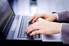 Hombre de negocios que pulsa en la computadora portátil Imagen de archivo libre de regalías