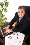 Hombre de negocios que pulsa en la computadora portátil en oficina Foto de archivo libre de regalías