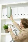 Hombre de negocios que quita la carpeta verde de estante Imagen de archivo libre de regalías