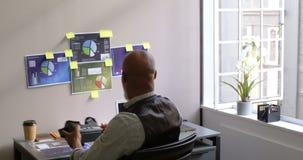 Hombre de negocios que quita las auriculares de la realidad virtual y que usa el ordenador portátil en el escritorio 4k almacen de metraje de vídeo