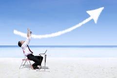 Hombre de negocios que ríe en la alegría que mira la muestra de la flecha del éxito la playa Foto de archivo