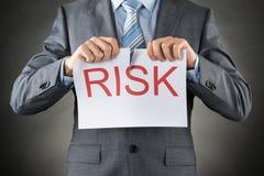 Hombre de negocios que rasga el riesgo de la palabra en el papel Imagen de archivo libre de regalías