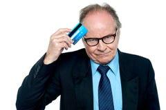 Hombre de negocios que rasguña su frente con la tarjeta plástica imagen de archivo