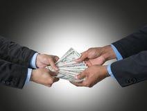 Hombre de negocios que recibe el dinero ofrecido por el hombre de negocios foto de archivo libre de regalías