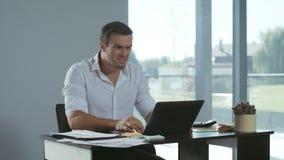 Hombre de negocios que recibe la mala letra por el correo electrónico Funcionamiento independiente serio en el ordenador portátil almacen de video