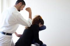 Hombre de negocios que recibe shiatsu en una silla del masaje Fotos de archivo