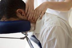 Hombre de negocios que recibe shiatsu en una silla del masaje Fotos de archivo libres de regalías