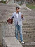 Hombre de negocios que recorre abajo de las escaleras Director que manda un SMS en el fondo urbano Concepto progresivo del negoci imagenes de archivo