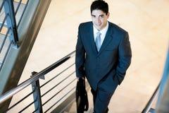 Hombre de negocios que recorre encima de las escaleras Foto de archivo libre de regalías