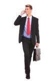 Hombre de negocios que recorre y que habla en el teléfono Imagen de archivo libre de regalías