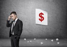 Hombre de negocios que reflexiona con el cartel de la muestra de dólar en fondo imagenes de archivo