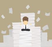 Hombre de negocios que reflexiona sobre una pila de división de los documentos Imagen de archivo