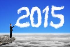 Hombre de negocios que rocía forma de la nube de 2015 años en cloudscap del cielo azul Imagenes de archivo