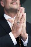 Hombre de negocios que ruega con el rosario Imagen de archivo libre de regalías