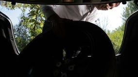 Hombre de negocios que saca la rueda de repuesto de tronco de coche almacen de video