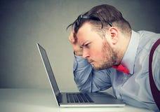 Hombre de negocios que saca sus vidrios que tienen problemas de la vista confundidos con el ordenador portátil fotografía de archivo libre de regalías
