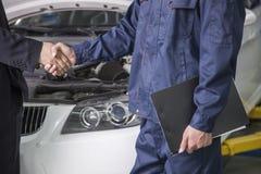 Hombre de negocios que sacude las manos con el mecánico en taller de reparaciones auto Imagen de archivo