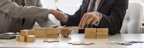Hombre de negocios que sacude las manos con los bloques de madera en el escritorio Fotografía de archivo libre de regalías
