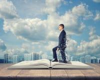 Hombre de negocios que sale del libro en fondo nublado de la ciudad Imagenes de archivo