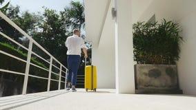 Hombre de negocios que sale de la casa moderna con una maleta amarilla almacen de metraje de vídeo