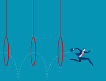 Hombre de negocios que salta a través de aros Fotografía de archivo libre de regalías