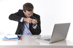 Hombre de negocios que señala el arma al ordenador en concepto del trabajo del trabajo excesivo y de tiempo suplementario Fotografía de archivo