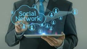 Hombre de negocios que señala en el cojín social de la tableta del concepto de la red almacen de video