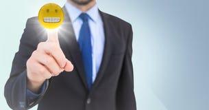 Hombre de negocios que señala en el emoji con la llamarada en fondo azul Foto de archivo