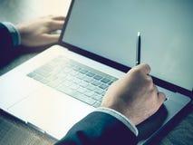 Hombre de negocios que señala en la pantalla de un ordenador portátil Fotografía de archivo libre de regalías