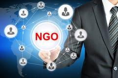 Hombre de negocios que señala en muestra de la ONG (organización no gubernamental) en la pantalla virtual Imagen de archivo
