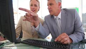 Hombre de negocios que señala en una pantalla con su colega metrajes