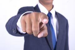Hombre de negocios que señala hacia en el fondo blanco Foto de archivo libre de regalías