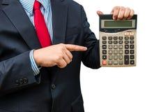 Hombre de negocios que señala a la calculadora en el fondo blanco Imagen de archivo