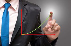 Hombre de negocios que señala o que toca con el gráfico superior en b azul marino Foto de archivo