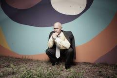 Hombre de negocios que se agacha en la obscuridad Imagenes de archivo