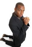 Hombre de negocios que se arrodilla haciendo un gesto del rezo Foto de archivo