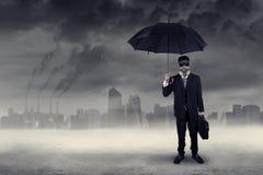 Hombre de negocios que se coloca al aire libre bajo contaminación atmosférica Foto de archivo libre de regalías