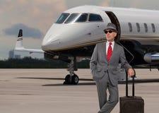 Hombre de negocios que se coloca al lado de un jet privado Imagen de archivo