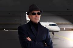 Hombre de negocios que se coloca al lado del jet privado Fotos de archivo