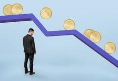 Hombre de negocios que se coloca bajo gráfico que cae con las monedas de oro que ruedan abajo Imagenes de archivo