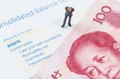 Hombre de negocios que se coloca con el billete de banco chino en el bala Imagen de archivo libre de regalías