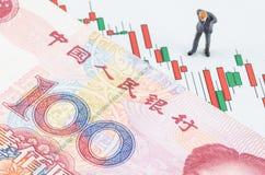 Hombre de negocios que se coloca con el billete de banco chino en el cand Imagen de archivo