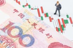 Hombre de negocios que se coloca con el billete de banco chino en el cand Foto de archivo
