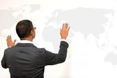 Hombre de negocios que se coloca con el mapa del mundo en la pared blanca Imagenes de archivo