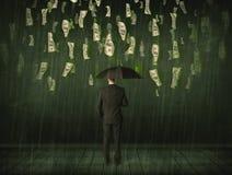 Hombre de negocios que se coloca con el paraguas en concepto de la lluvia del billete de dólar Imagen de archivo libre de regalías