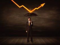 Hombre de negocios que se coloca con el paraguas que guarda la flecha anaranjada Fotografía de archivo