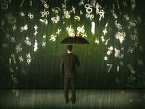 Hombre de negocios que se coloca con el paraguas y números 3d que llueven el concep Fotografía de archivo